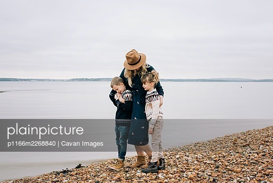 Mom and her kids walking along the beach hugging on a calm autumn day - p1166m2268840 by Cavan Images