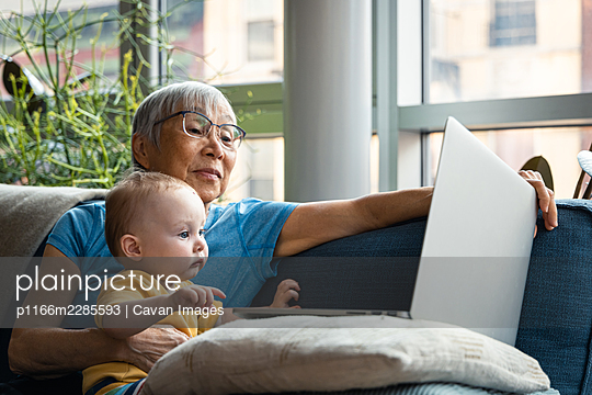 Senior Grandparent and Granddaughter looking at computer together - p1166m2285593 by Cavan Images