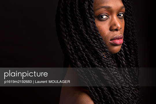 Portrait of a young black woman with long braid - p1619m2192683 by Laurent MOULAGER