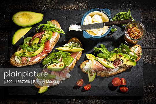 Onion bread with cream cheese, parma ham, avocado, rucola, thyme and tomato - p300m1587056 von Roman Märzinger