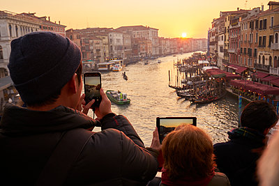 Group of people using smartphones to capture the sunset, Venice - p1312m2082234 by Axel Killian