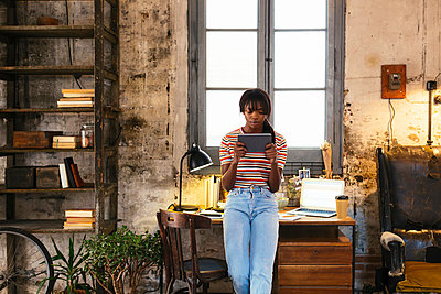 Young woman standing in front of desk in a loft using tablet - p300m1581299 by Bonninstudio