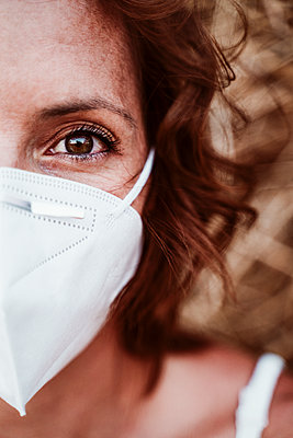 Close-up of woman wearing face mask against hay during pandemic - p300m2206643 by Eva Blanco