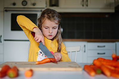 Girl cutting carrot - p312m2191147 by Matilda Holmqvist