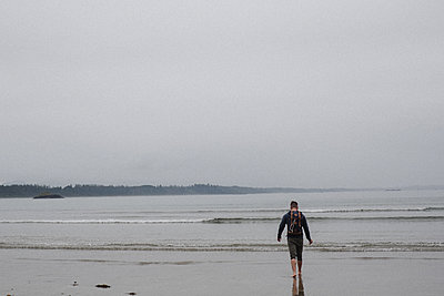 Man on beach, Tofino, Canada - p924m2016389 by Kymberlie Dozois Photography