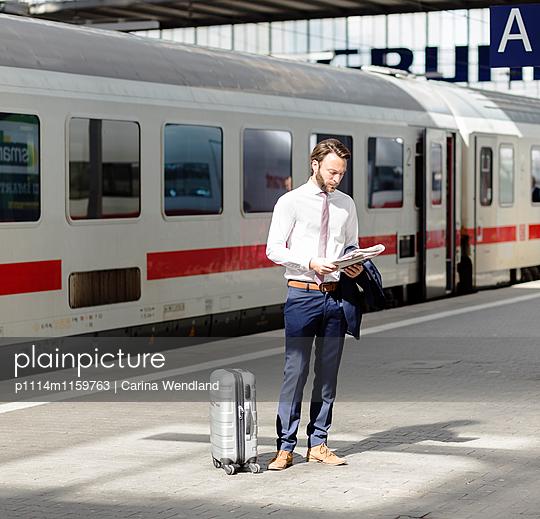Geschäftsmann am Bahnsteig liest Zeitung - p1114m1159763 von Carina Wendland