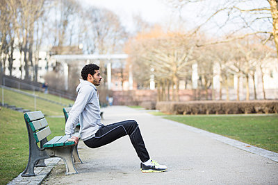 Man in sports clothing doing push-ups on bench - p1026m1139951 by Patrick Frost