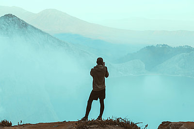 Young man looking at Ijen lake - p1166m2137435 by Cavan Images