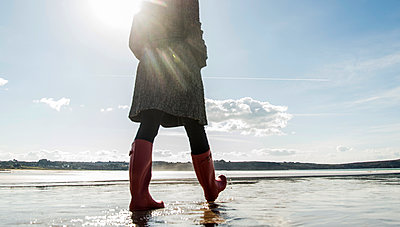 France, Bretagne, Finistere, Crozon peninsula, woman walking on the beach - p300m1127603f by Uwe Umstätter