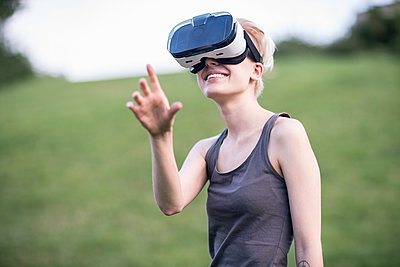 Smiling young woman using Virtual Reality Glasses outdoors - p300m1206030 by A. Tamboly