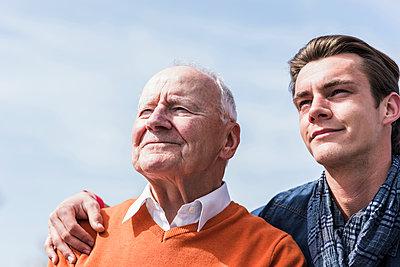 Smiling senior man and adult grandson outdoors - p300m1449765 by Uwe Umstätter