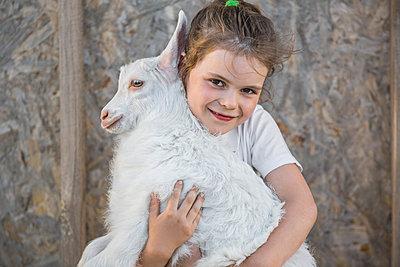 Portrait of cute girl holding baby goat outdoors - p301m961120f by Vladimir Godnik