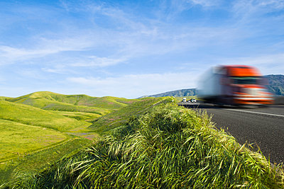 Truck driving on remote road in rolling landscape - p555m1420861 by PBNJ Productions