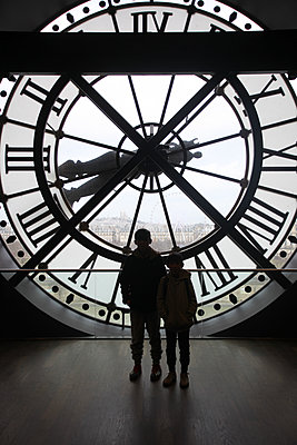 Two children in front of a Giant clock - p664m2151471 by Yom Lam
