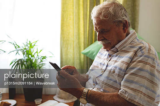 Senior man using mobile phone at nursing home - p1315m2091184 by Wavebreak