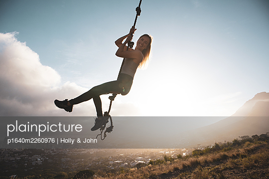 Blond woman swings on a rope, city in background - p1640m2260976 by Holly & John