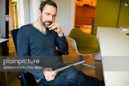 Businessman using tablet at desk in office - p300m2131616 by Fritz Miller