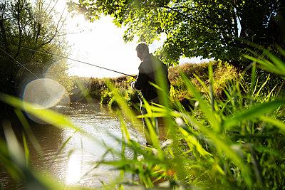 Man fly fishing at sunny idyllic summer river - p1023m2262066 by Martin Barraud