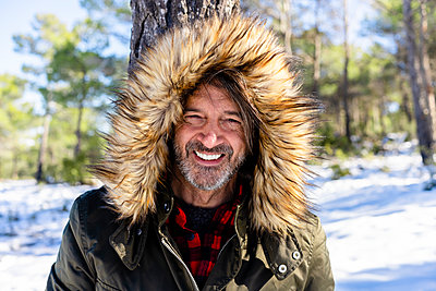 Mature man wearing fur hood smiling while standing in forest - p300m2250922 by Javier De La Torre Sebastian