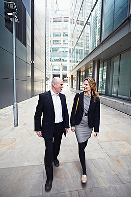 Businessman and businesswoman walking past office buildings - p429m803588f by Liam Norris