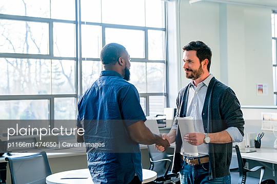 Businessmen doing handshake while standing in office
