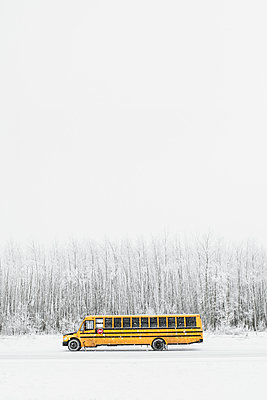 School bus parked on a snowy day in Calgary, Canada with negative spac - p1166m2078376 by Cavan Images