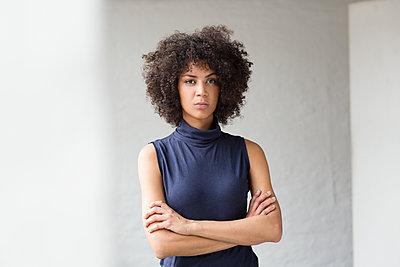 Hübsche Geschäftsfrau mit Afro verschränkt ihre Arme  - p1301m2020279 von Delia Baum