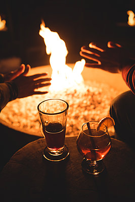 Midsection of couple sitting by fire pit and drinks - p1315m1421862 by Wavebreak