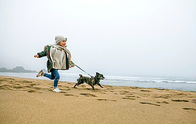 Happy girl running with dog on the beach on a foggy winter day - p300m1228352 by David Pereiras