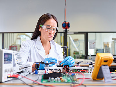 Female technician working in research laboratory, connecting plug of drone - p300m2113961 by Christian Vorhofer