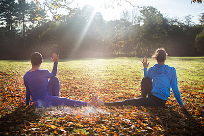 Two women doing yoga in park on autumn day - p429m1224202 by Bonfanti Diego