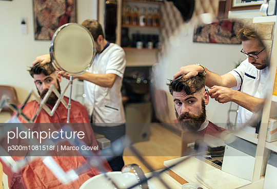 Reflection of barber cutting hair of a customer - p300m1081518f by Marco Govel