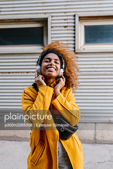 Smiling Afro woman with eyes closed listening music through headphones against wall - p300m2265308 by Ezequiel Giménez
