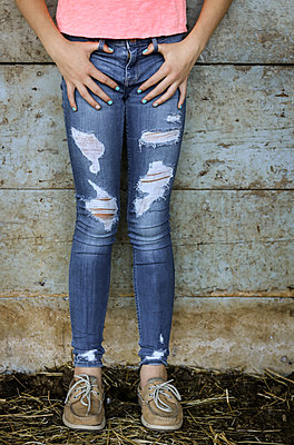 Teenage Girl legs in jeans in a Barn  - p1019m1487225 by Stephen Carroll
