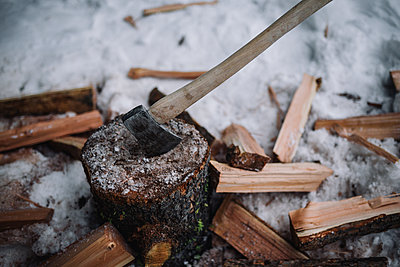 A wood handled axe sticks into a log with firewood and snow around it - p1166m2247296 by Cavan Images