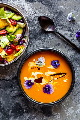 Bowl of mixed salad with edible flowers and bowl of creamed pumpkin soup garnished with edible flowers - p300m2059347 by Sandra Roesch
