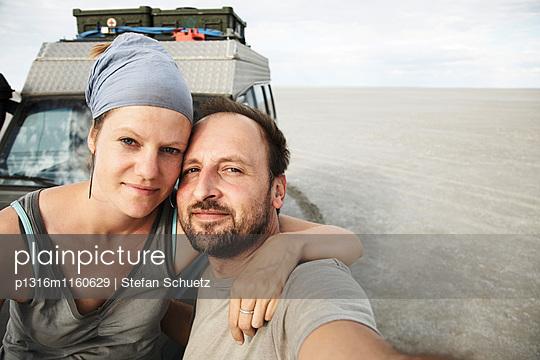 Paar steht vor einem Geländewagen, Kubu Island, Makgadikgadi-Salzpfannen, Botswana - p1316m1160629 von Stefan Schuetz