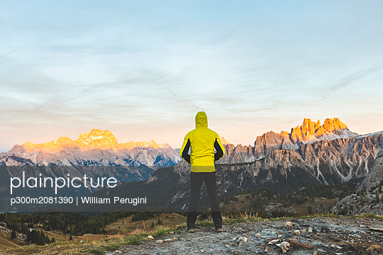 Italy, Tre Cime di Lavaredo, man enjoying colourful mountain peaks at sunset - p300m2081390 by William Perugini
