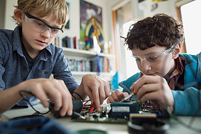 Focused boys assembling circuit board - p1192m1129533f by Hero Images