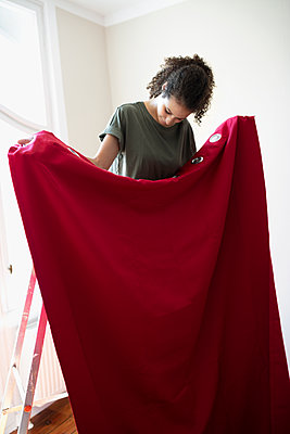 Women hanging red curtain - p1192m2016664 by Hero Images