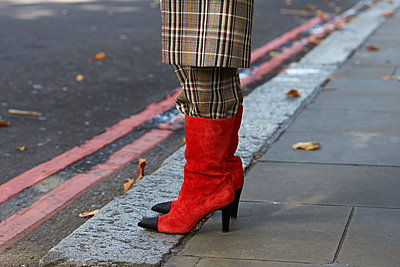 Woman in brown check coat and trousers tucked into red boots - p1407m1545422 by Guerrilla