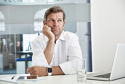 Bored and frustated businessman at desk - p300m1047510f by Philipp Dimitri