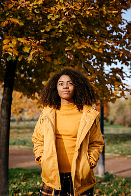 Beautiful Afro woman with hands in pockets standing in park during sunny day - p300m2268153 by Tania Cervián