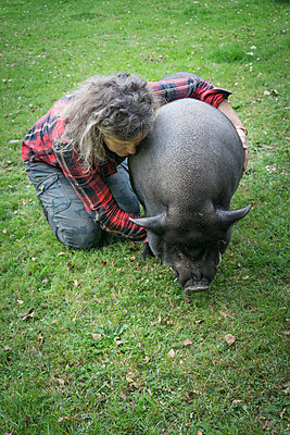 Woman embracing domestic pig - p403m1502462 by Helge Sauber