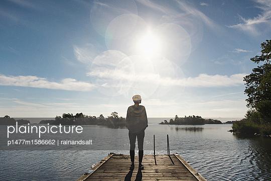 Junge Frau auf einem Bootssteg mit Lens Flare - p1477m1586662 von rainandsalt