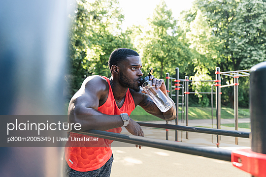 Young athlete training on parallel bars, outdoors, drinking water - p300m2005349 von Uwe Umstätter