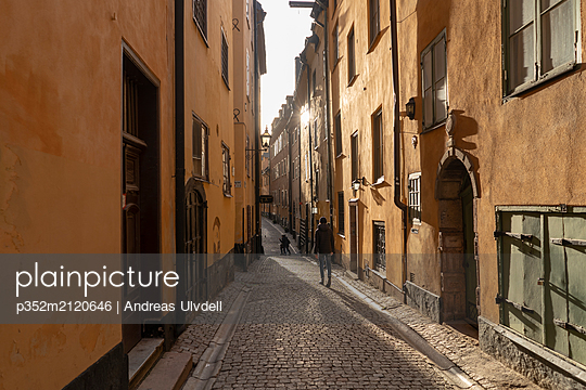 Teenage boy walking on alley in old town of Stockholm, Sweden - p352m2120646 by Andreas Ulvdell