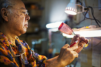 A senior craftsman at work in a glass maker's studio workshop, in inspecting red wine glass with cut glass decoration against the light.  - p1100m1185842 by Mint Images