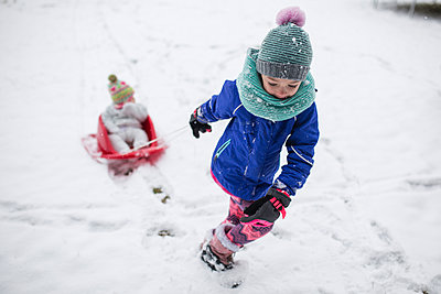 Girl pulling sister sitting in sled on snow covered field - p1166m1474064 by Cavan Images