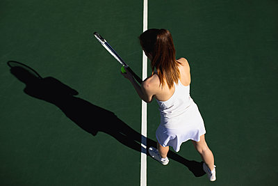 Woman playing tennis on a sunny day - p1315m2131514 by Wavebreak
